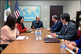 Secretary Whitley sitting in a conference room with Mexican Consul General, Carlos Cue Vega and staff