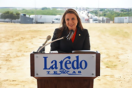Secretary Hughs standing behind a podium that has a Laredo sign.